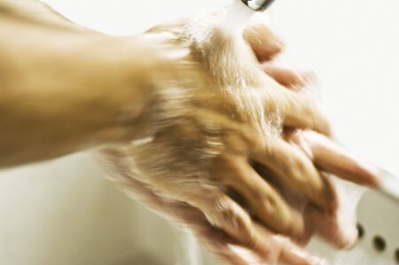 a man is washing hands in washstand Stock Photo