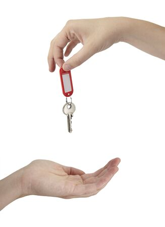 in escrow: A female is handing over the keys on a white background Stock Photo