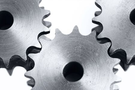 three metal cogs on a white background
