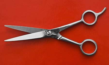 a pair of Scissors on red background