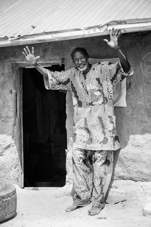 third age: PORTO-NOVO, BENIN - MAR 8, 2012: Unidentified funny Beninese man waves hands and smiles. People of Benin suffer of poverty due to the difficult economic situation. Editorial