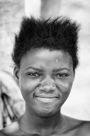 third world: PORTO-NOVO, BENIN - MAR 8, 2012: Unidentified Beninese smiling woman with stylish hair. People of Benin suffer of poverty due to the difficult economic situation.