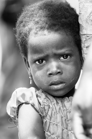 shy girl: PORTO-NOVO, BENIN - MAR 8, 2012: Unidentified Beninese little shy girl with sad eyes stays near the tree. People of Benin suffer of poverty due to the difficult economic situation. Editorial