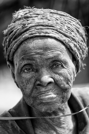 PORTO-NOVO, BENIN - MAR 8, 2012: Unidentified Beninese old woman tries to smile for the camera. People of Benin suffer of poverty due to the difficult economic situation. Editorial