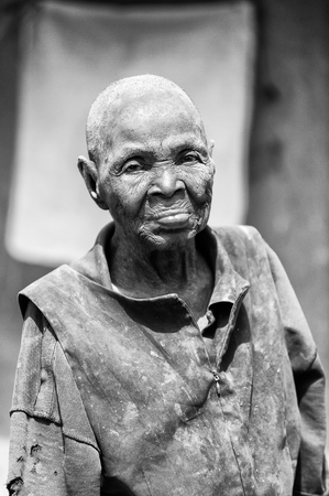 colorless: PORTO-NOVO, BENIN - MAR 8, 2012: Unidentified Beninese hairless woman smiles sincerely. People of Benin suffer of poverty due to the difficult economic situation. Editorial