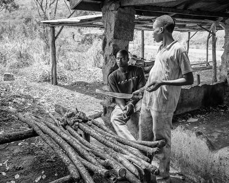unicef: Porto-Novo, Benin - MAR 8, 2012: non identificato uomo beninese cucina sul legno. La gente del Benin soffrono di povert� a causa della difficile situazione economica. Editoriali