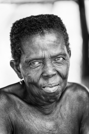 unicef: PORTO-NOVO, BENIN - MAR 8, 2012: Portrait of unidentified Beninese sympathic old woman. People of Benin suffer of poverty due to the difficult economic situation.