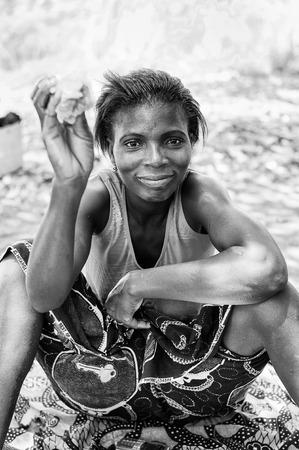 PORTO-NOVO, BENIN - 8 MARZO 2012: La bella ragazza simpatica beniniana non identificata vende i piatti e l'alimento. La gente del Benin soffre di povertà a causa della difficile situazione economica.