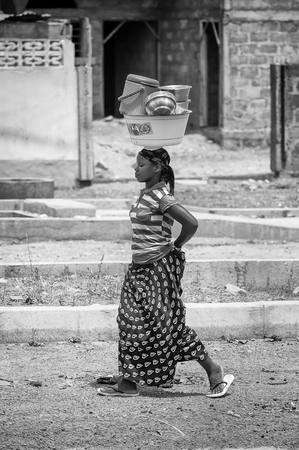 unicef: PORTO-NOVO, BENIN - MAR 8, 2012: Unidentified Beninese beautiful girl carries the dishes on her head. People of Benin suffer of poverty due to the difficult economic situation. Editoriali