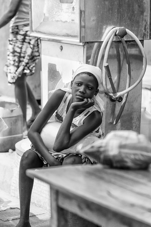 unicef: PORTO-NOVO, BENIN - MAR 8, 2012: Unidentified Beninese beautiful girl is bored working at the market. People of Benin suffer of poverty due to the difficult economic situation. Editoriali