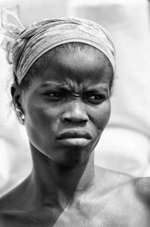 third eye: PORTO-NOVO, BENIN - MAR 8, 2012: Unidentified Beninese angry girl works at the market. People of Benin suffer of poverty due to the difficult economic situation.