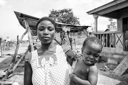 unicef: PORTO-NOVO, BENIN - MAR 8, 2012: Unidentified Beninese mother carries her little child in her hands People of Benin suffer of poverty due to the difficult economic situation.