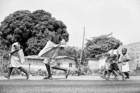 unicef: PORTO-NOVO, BENIN - MAR 8, 2012: Unidentified Beninese children run in the street. People of Benin suffer of poverty due to the difficult economic situation.