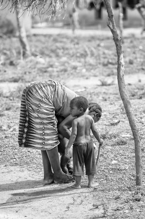 PORTO-NOVO, BENIN - 8 OTTOBRE 2012: La donna Benident non identificata gioca con i suoi figli. Le persone di Benin soffrono di povertà a causa della difficile situazione economica.
