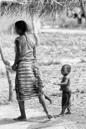 unicef: PORTO-NOVO, BENIN - MAR 8, 2012: Unidentified Beninese woman plays with her children. People of Benin suffer of poverty due to the difficult economic situation. Editoriali