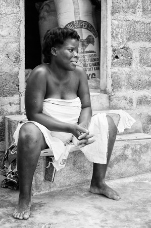 third age: PORTO-NOVO, BENIN - MAR 8, 2012: Unidentified Beninese woman sits in the street. People of Benin suffer of poverty due to the difficult economic situation.