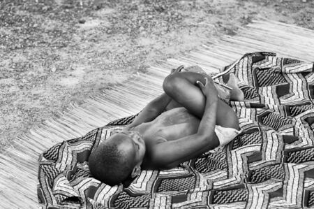 unicef: PORTO-NOVO, BENIN - MAR 8, 2012: Unidentified Beninese little boy plays on the ground. People of Benin suffer of poverty due to the difficult economic situation.