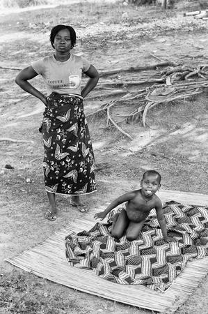 Porto-Novo, Benin - MAR 8, 2012: non identificato bambino beninese gioca sulla terra con la madre. La gente del Benin soffrono di povertà a causa della difficile situazione economica.