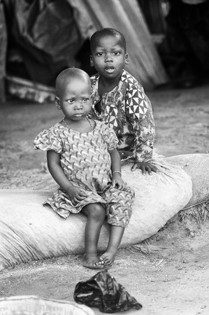 third world: PORTO-NOVO, BENIN - MAR 8, 2012: Unidentified Beninese children sit in the street. People of Benin suffer of poverty due to the difficult economic situation.
