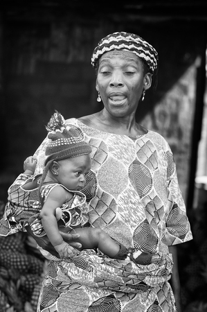 PORTO-NOVO, BENIN - MAR 8, 2012: Unidentified Beninese little beautiful child in a blue hat on his mother arms. People of Benin suffer of poverty due to the difficult economic situation.