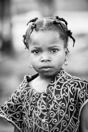 unicef: PORTO-NOVO, BENIN - MAR 8, 2012: Unidentified Beninese beautiful girl with small pigtails. People of Benin suffer of poverty due to the difficult economic situation.