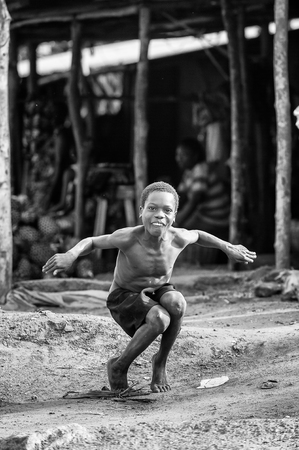 unicef: PORTO-NOVO, BENIN - MAR 8, 2012: Unidentified Beninese little boy jumps imitatiing a duck. People of Benin suffer of poverty due to the difficult economic situation. Editoriali