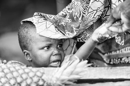 PORTO-NOVO, BENIN - 8 MARZO 2012: La bambina beniniana non identificata raggiunge una caramella. La gente del Benin soffre di povertà a causa della difficile situazione economica. Editoriali