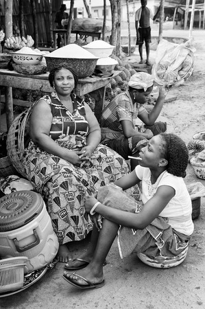 unicef: PORTO-NOVO, BENIN - MAR 8, 2012: Unidentified Beninese woman and her daughter work at market. People of Benin suffer of poverty due to the difficult economic situation.