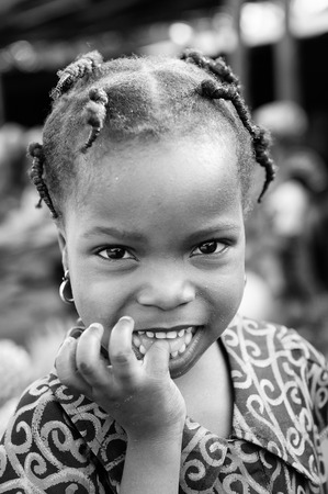 PORTO-NOVO, BENIN - MAR 8, 2012: Unidentified Beninese little smiling girl with pigtails. People of Benin suffer of poverty due to the difficult economic situation. Editoriali
