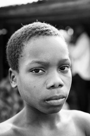 PORTO-NOVO, BENIN - 8 MARZO 2012: La ragazza beniniana non identificata osserva pacificamente sulla macchina fotografica. La gente del Benin soffre di povertà a causa della difficile situazione economica.