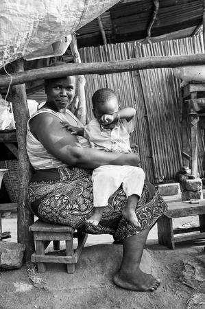 unicef: Porto-Novo, Benin - MAR 9, 2012: non identificato del Benin grasso donna sorridente gioca con il suo piccolo figlio sul mercato. La gente del Benin soffrono di povertà a causa della difficile situazione economica. Editoriali