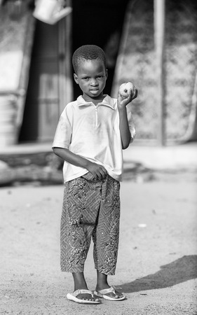 PORTO-NOVO, BENIN - MAR 9, 2012: Unidentified Beninese little boy with a apple at the market. People of Benin suffer of poverty due to the difficult economic situation.