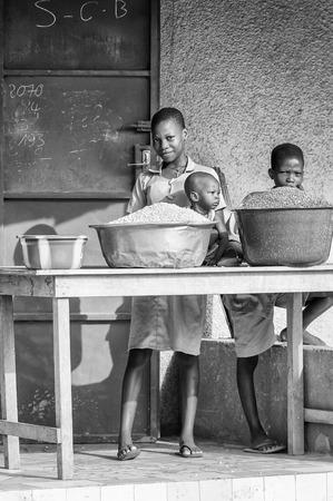 unicef: Porto-Novo, Benin - MAR 9, 2012: non identificato ragazza beninese vende cereali con i suoi figli. La gente del Benin soffrono di povertà a causa della difficile situazione economica. Editoriali