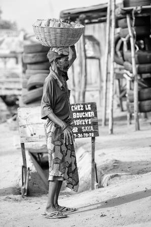 PORTO-NOVO, BENIN - 9 MARZO 2012: L'uomo beniniano non identificato vende le verdure dal canestro sulla sua testa. La gente del Benin soffre di povertà a causa della difficile situazione economica.