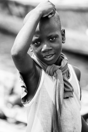 PORTO-NOVO, BENIN - MAR 9, 2012: Unidentified Beninese  boy in a fishing boat. People of Benin suffer of poverty due to the difficult economic situation.
