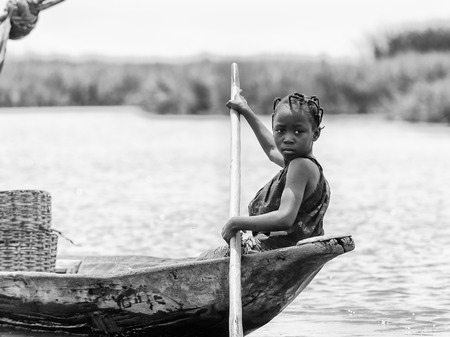 PORTO-NOVO, BENIN - MAR 9, 2012: Unidentified Beninese beautiful little girl raws the boar for fishing. People of Benin suffer of poverty due to the difficult economic situation. Editorial