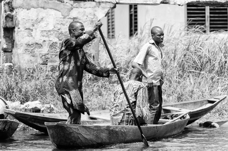 PORTO-NOVO, BENIN - MAR 9, 2012: Unidentified Beninese  men sail a wooden boat. People of Benin suffer of poverty due to the difficult economic situation.