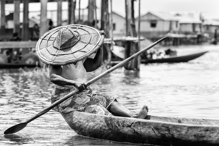 colorless: PORTO-NOVO, BENIN - MAR 9, 2012: Unidentified Beninese  woman sails a wooden boat. People of Benin suffer of poverty due to the difficult economic situation.