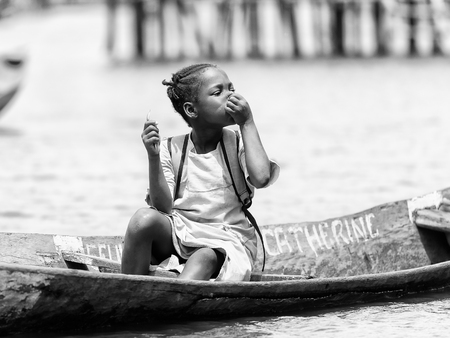 colorless: PORTO-NOVO, BENIN - MAR 9, 2012: Unidentified Beninese  little girl in a wooden boat. People of Benin suffer of poverty due to the difficult economic situation.
