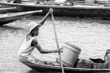 PORTO-NOVO, BENIN - MAR 9, 2012: Unidentified Beninese   girl sails a wooden boat. People of Benin suffer of poverty due to the difficult economic situation. Editorial