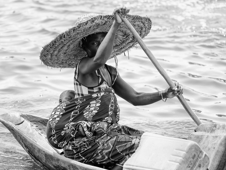 PORTO-NOVO, BENIN - MAR 9, 2012: Unidentified Beninese woman with her child on her back rows a wooden boat. People of Benin suffer of poverty due to the difficult economic situation. Editorial