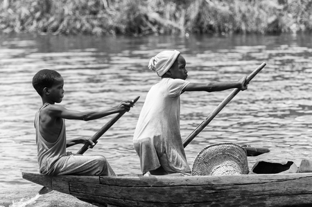 PORTO-NOVO, BENIN - MAR 9, 2012: Unidentified Beninese little boy and girl row a wooden boat. People of Benin suffer of poverty due to the difficult economic situation. Editorial