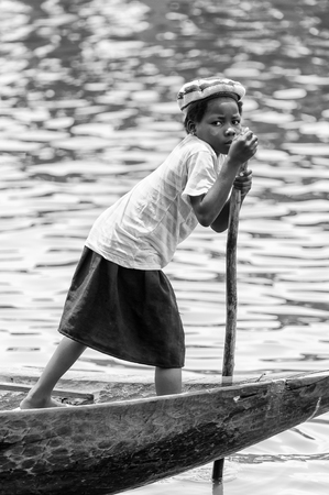 colorless: PORTO-NOVO, BENIN - MAR 9, 2012: Unidentified Beninese little girl rows in a wooden boat. People of Benin suffer of poverty due to the difficult economic situation. Editorial