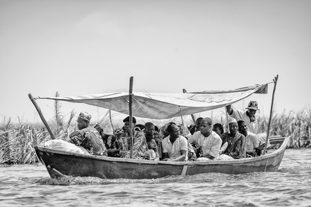people in row: PORTO-NOVO, BENIN - MAR 9, 2012: Unidentified Beninese people row a wooden boat. People of Benin suffer of poverty due to the difficult economic situation