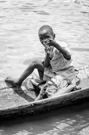 PORTO-NOVO, BENIN - MAR 9, 2012: Unidentified Beninese little boy in a wooden boat. People of Benin suffer of poverty due to the difficult economic situation.
