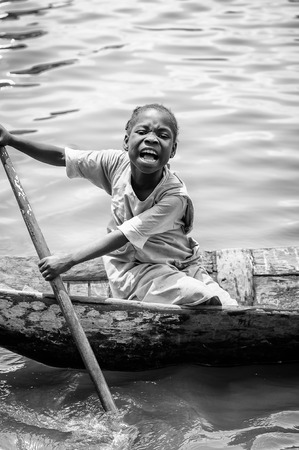 colorless: PORTO-NOVO, BENIN - MAR 9, 2012: Unidentified Beninese little girl rows a wooden boat. People of Benin suffer of poverty due to the difficult economic situation.