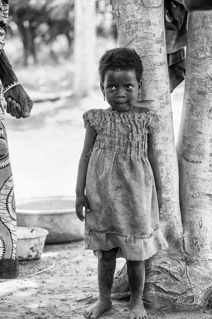third age: PORTO-NOVO, BENIN - MAR 8, 2012: Unidentified Beninese little girl in a blue dress stays near the tree. People of Benin suffer of poverty due to the difficult economic situation. Editorial