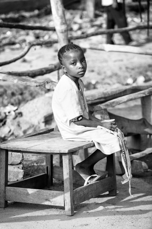 unicef: PORTO-NOVO, BENIN - MAR 8, 2012: Unidentified Beninese girl sits on the wooden table. People of Benin suffer of poverty due to the difficult economic situation.