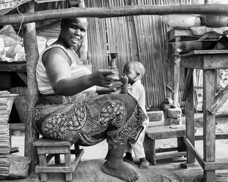unicef: PORTO-NOVO, BENIN - MAR 9, 2012: Unidentified Beninese fat smiling woman plays with her little son in the market. People of Benin suffer of poverty due to the difficult economic situation.
