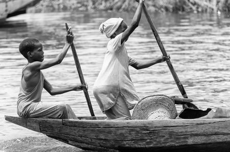 colorless: PORTO-NOVO, BENIN - MAR 9, 2012: Unidentified Beninese little boy and girl row a wooden boat. People of Benin suffer of poverty due to the difficult economic situation. Editorial